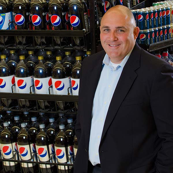 Employee standing next Pepsi display