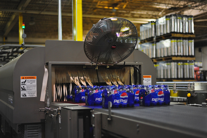 Pepsi bottles being shrink wrapped on the production line