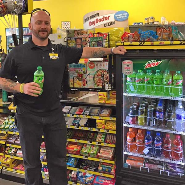 Employee standing next to stock beverage cooler